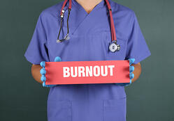 Doctor in scrubs holding red burnout sign_small