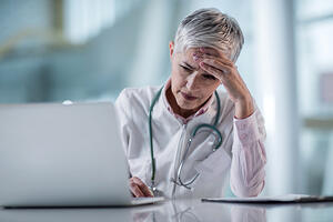 Female Physician Stress Looking at Laptop