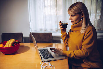 Female Middle Aged Remote Employee Drinking Wine on Job_Small