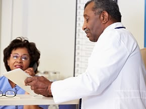 older physician speaking with assistant