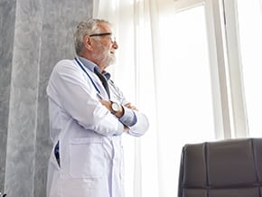 graying physician stares longingly out the window, pondering inquisitively about the winnowing of the labor force