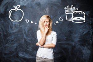 Woman makes a choice between bad food and healthy eating