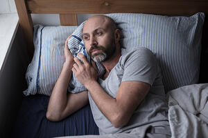 Man with depression laying in bed_mental health