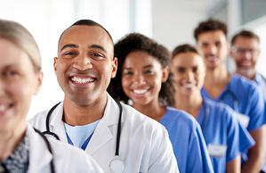young male africian american doctor and team_smiling