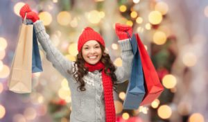 holidays - happy young woman in winter clothes with shopping bags over lights background