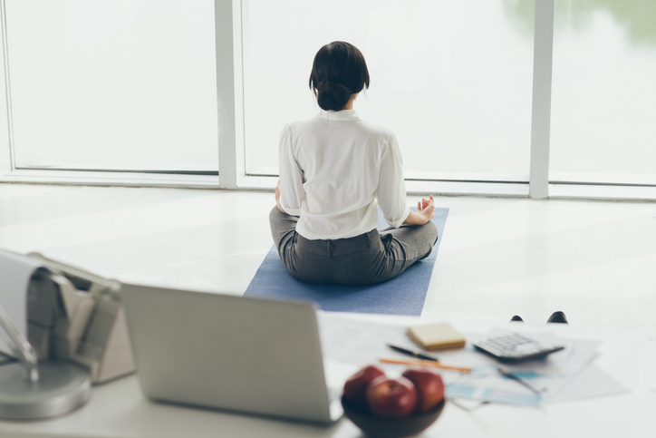 Woman meditating in office looking out window